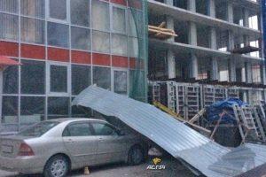 """На стройке в Новосибирске ветер """"уронил"""" забор на иномарку"""