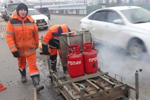Дорожники делают ямочный ремонт после оттепели на Октябрьском мосту